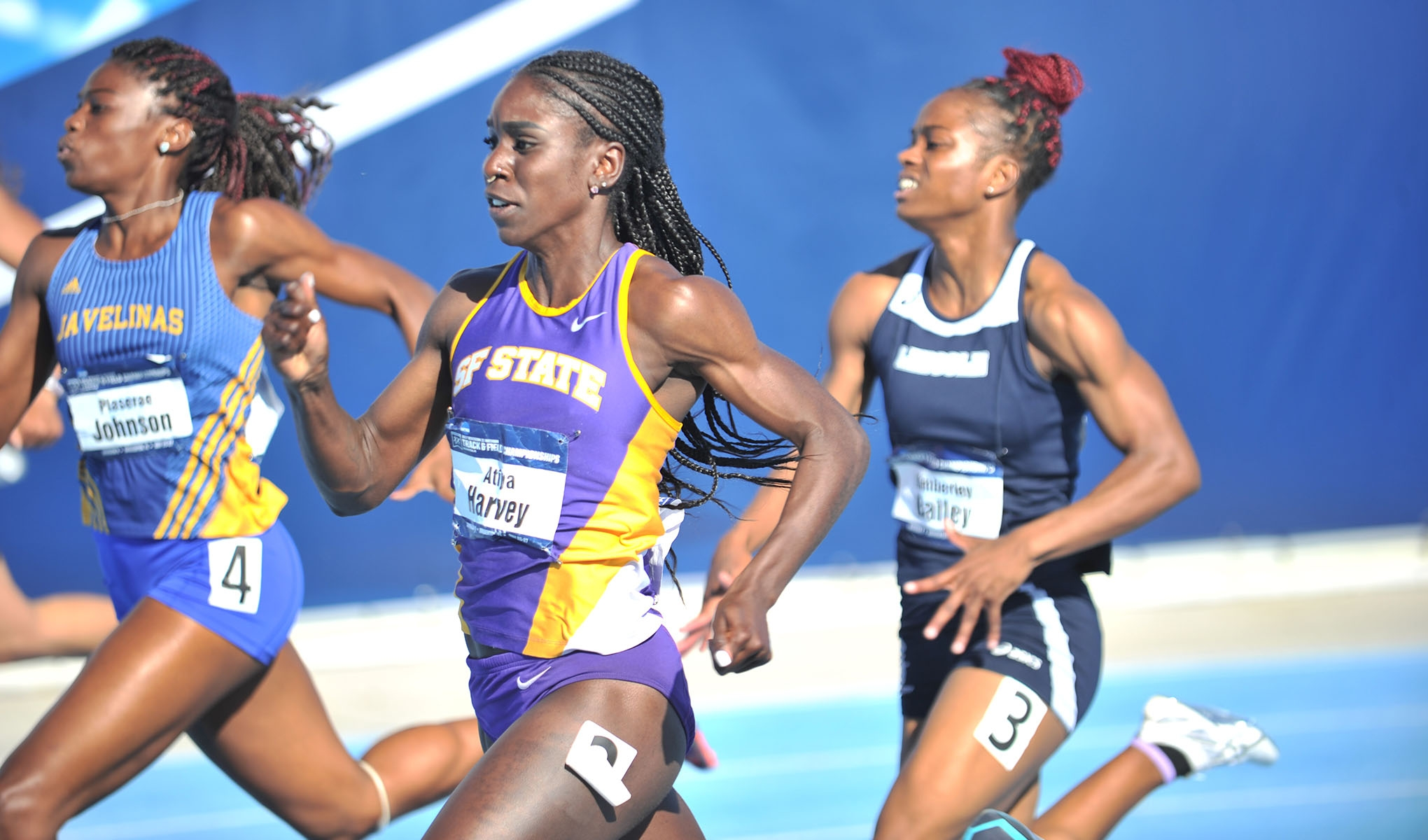 Atiya Harvey runs next to two competitors during her leg of the women's 4x400 relay competition.