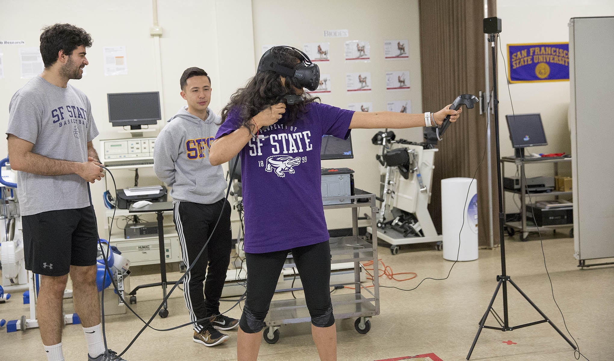 A purple-shirted student wearing a headset plays a virtual reality game as two other students look on.