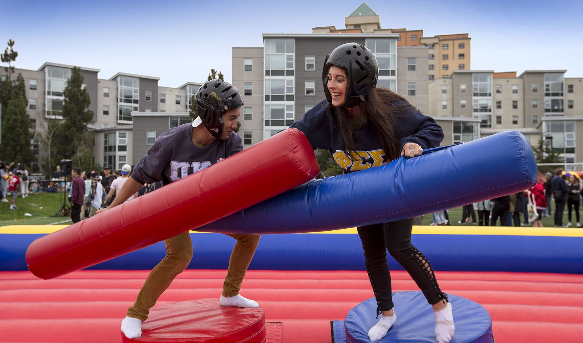 A female and male student try to knock each other off blocks using foam batons.