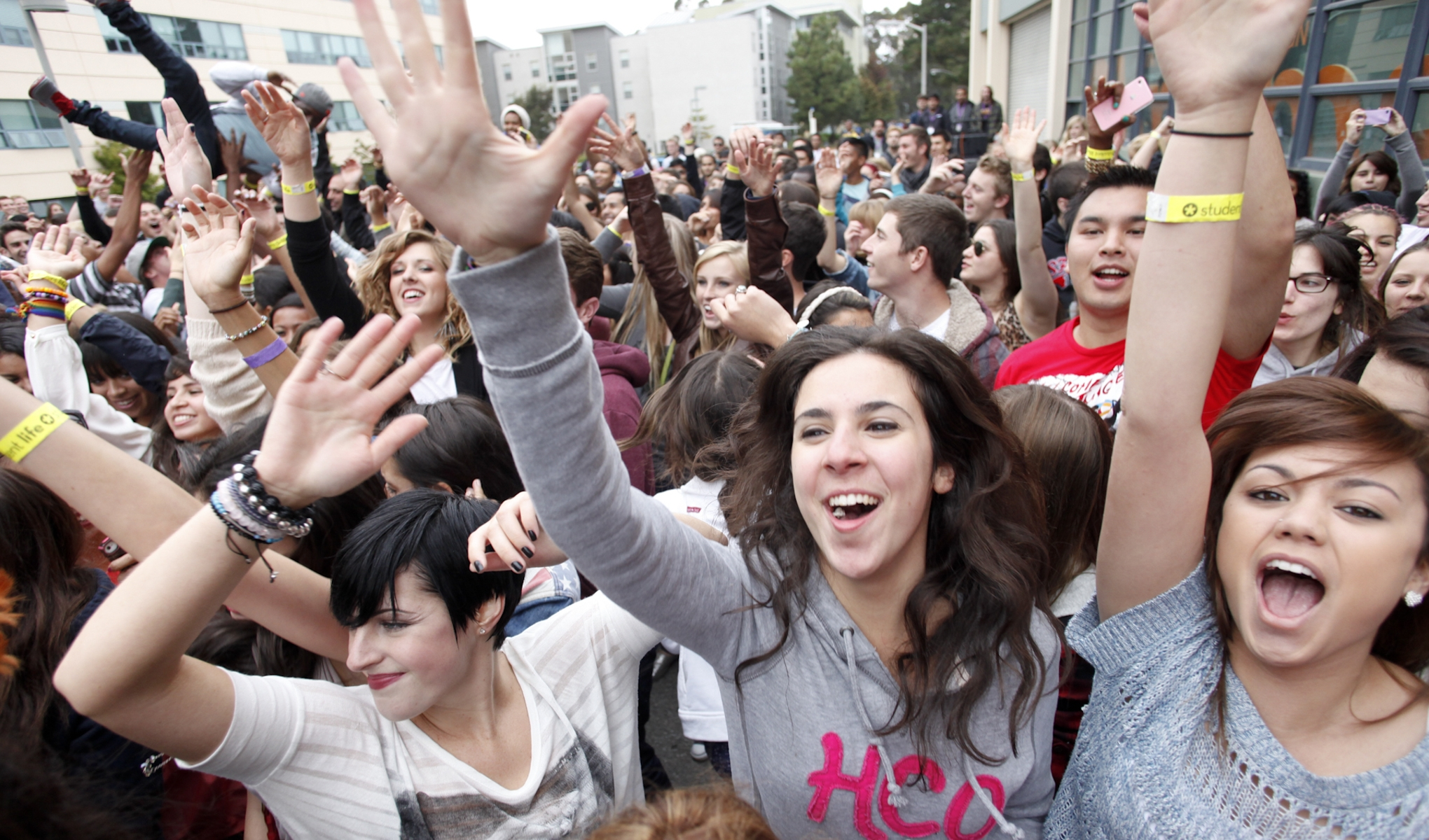 A large crowd of smiling students each raise a hand in the air