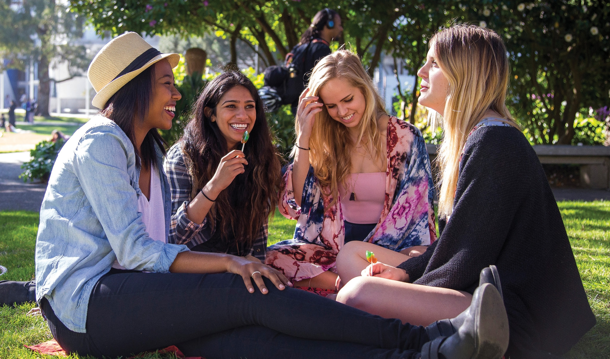 Four female students sitting and talking on a grass field on SFSU campus