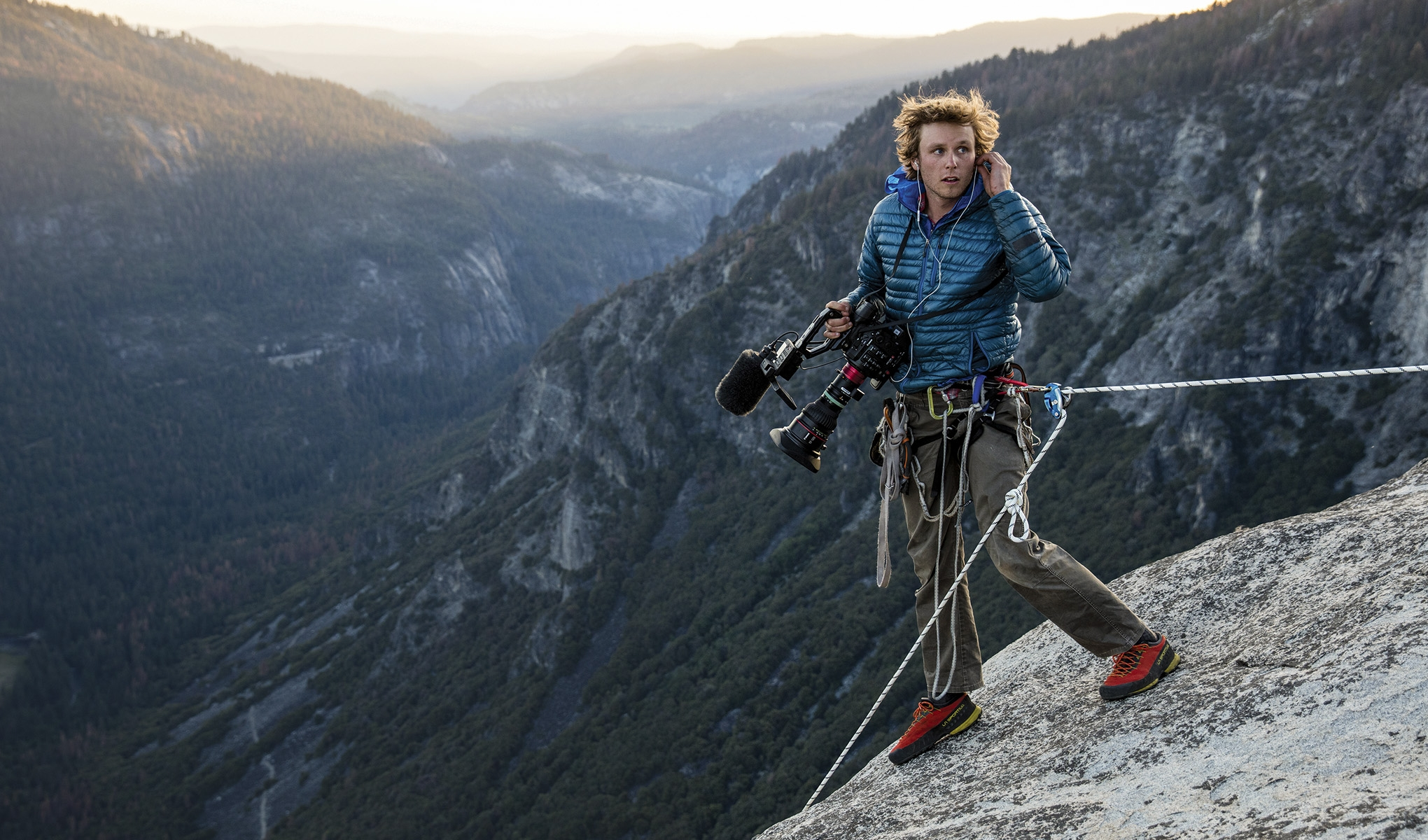 Sammuel Crossley holding a camera while strapped into a harness on top of a mountain