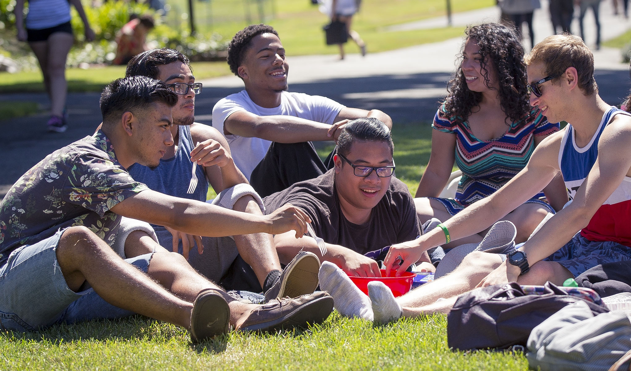Students hanging out on a grassy field picking snacks from a red bowl