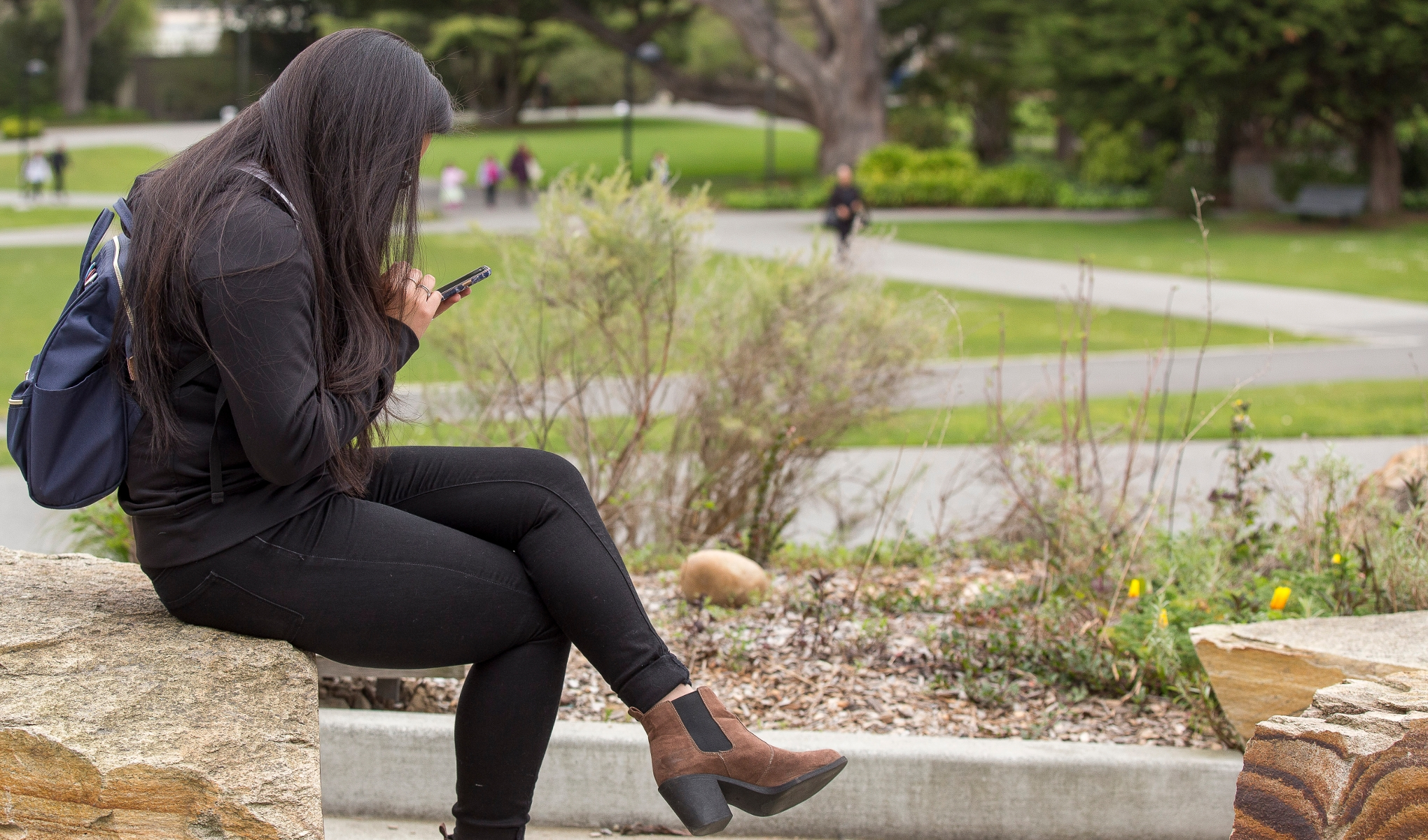 Student hunched over, looking down at phone