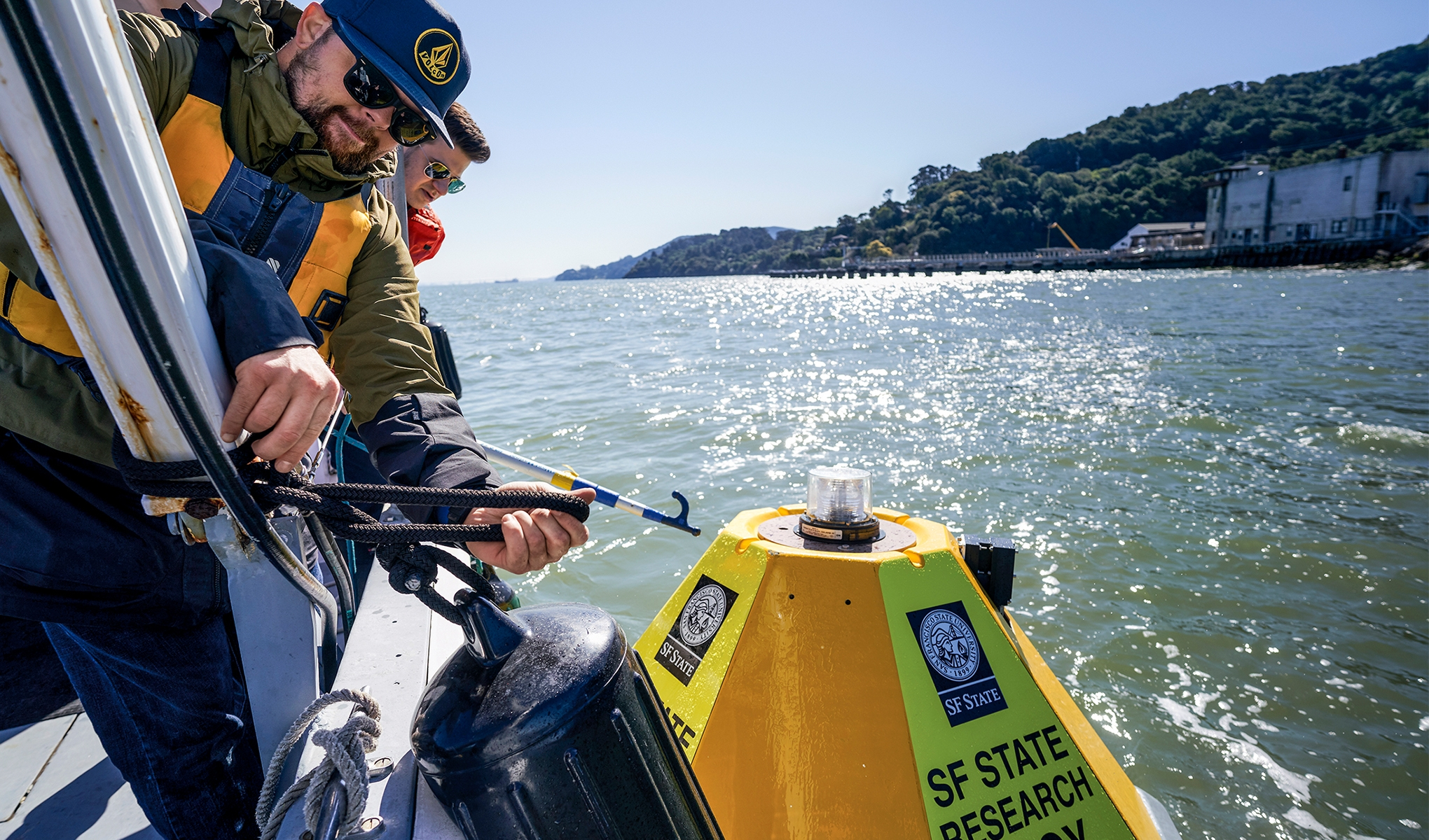 Researchers on a boat drop research buoy into bay area waters