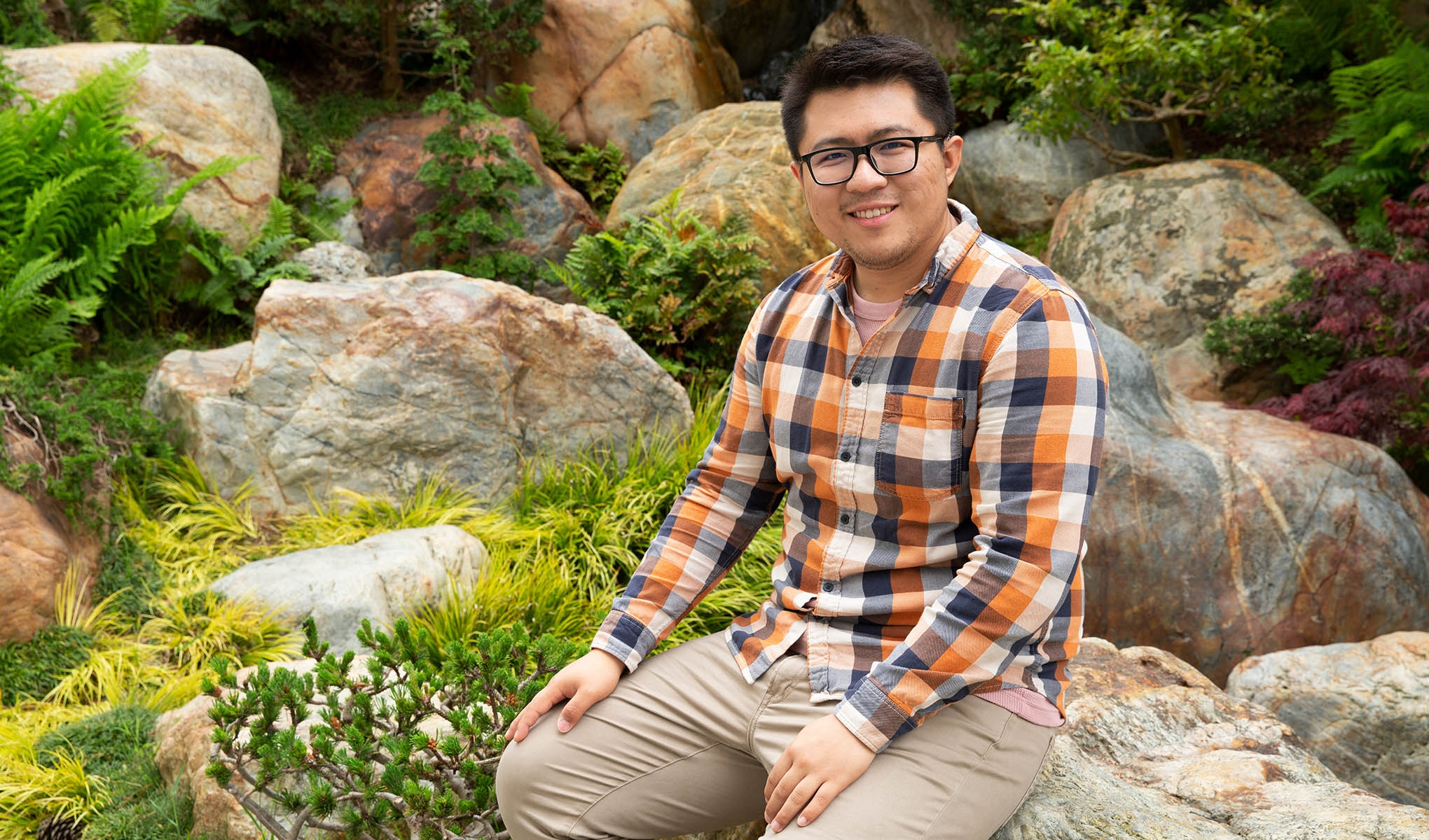Cheng Yu poses in front of greenery