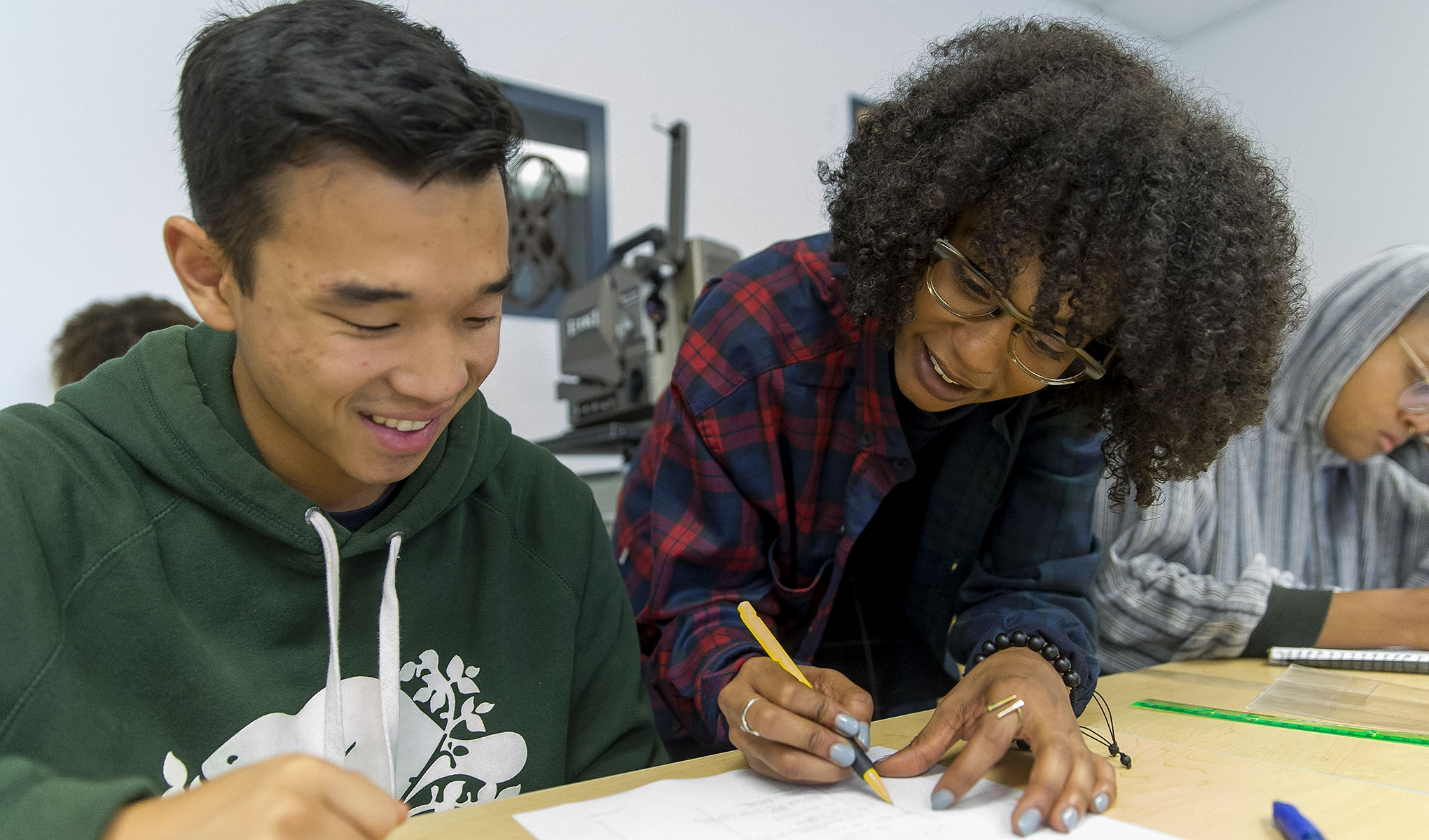 Female helping male student with written work